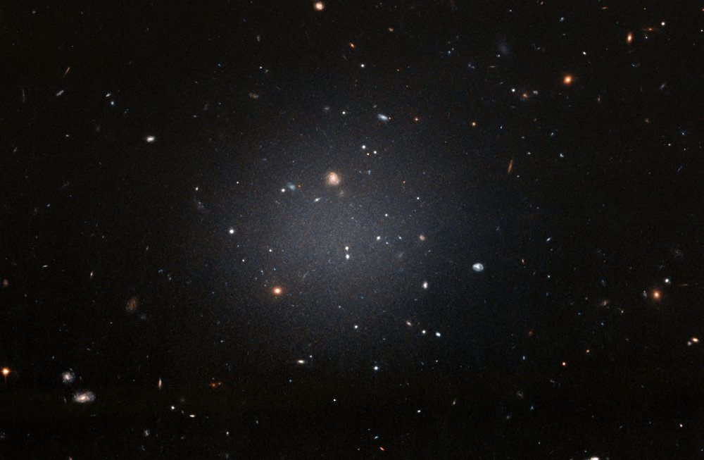 NGC 1052-DF2 resides about 65 million light-years away in the NGC 1052 Group, which is dominated by a massive elliptical galaxy called  NGC 1052 .  This large, fuzzy-looking galaxy is so diffuse that astronomers can clearly see distant galaxies behind it. This ghostly galaxy is not well-formed. It does not look like a typical  spiral galaxy , but it does not look like an  elliptical galaxy  either. Based on the colours of its globular clusters, the galaxy is about 10 billion years old. However, even the globular clusters are strange: they are twice as large as typical groups of stars. - Image Credit: NASA, ESA, and P. van Dokkum (Yale University) (click to enlarge)