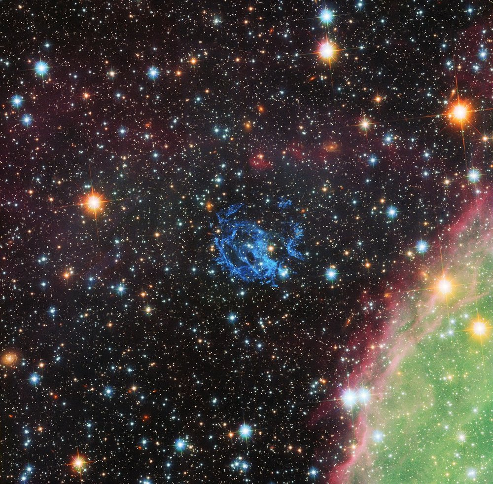 This picture from the  NASA/ESA Hubble Space Telescope sets the scene for the story of the hunt for an elusive missing object hidden amid a complex tangle of gaseous filaments in one of our nearest neighbouring galaxies, the  Small Magellanic Cloud .  The wisps of gas forming the supernova remnant 1E 0102.2-7219 show up in blue near the centre of the picture. Part of the massive star-forming region, N 76, also known as Henize 1956, appears at the lower right in green and pink. - Image Credit: NASA , ESA and the Hubble Heritage Team ( STScI / AURA )