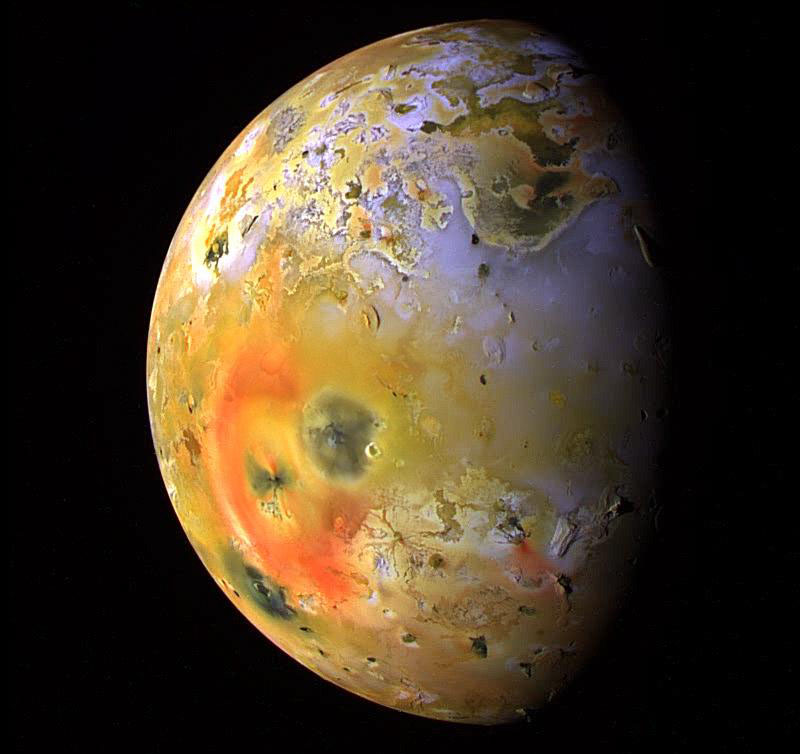 """Io is captured here by NASA's Galileo spacecraft. Deposits of sulfur dioxide frost appear in white and grey hues while yellowish and brownish hues are probably due to other sulfurous materials. Bright red materials, such as the prominent ring surrounding Pele (lower left), and """"black"""" spots mark areas of recent volcanic activity. - Image Credit: NASA / JPL / University of Arizona"""