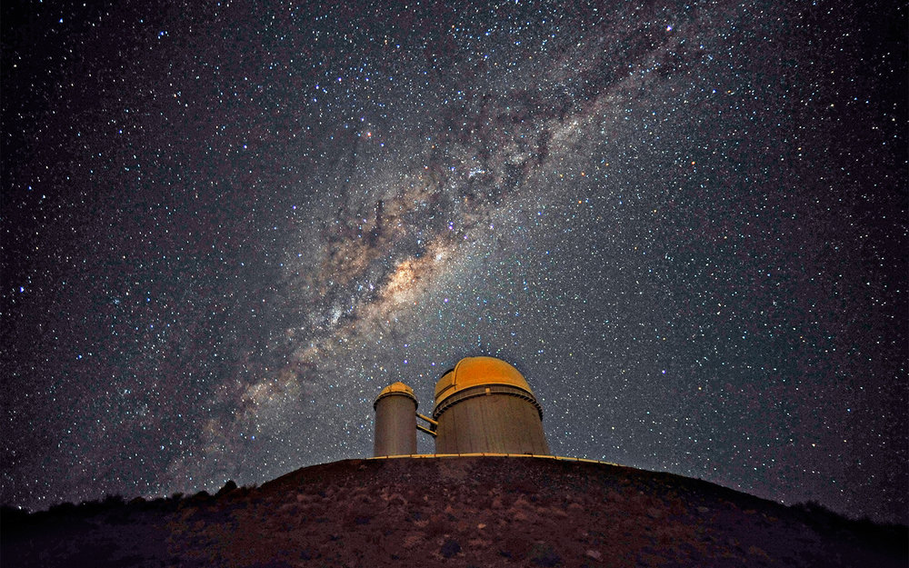 The Milky Way, our own galaxy, stretches across the sky above the La Silla telescope in Chile. Hidden inside our own galaxy are trillions of planets, most waiting to be found. - Image Credits: ESO/S. Brunier