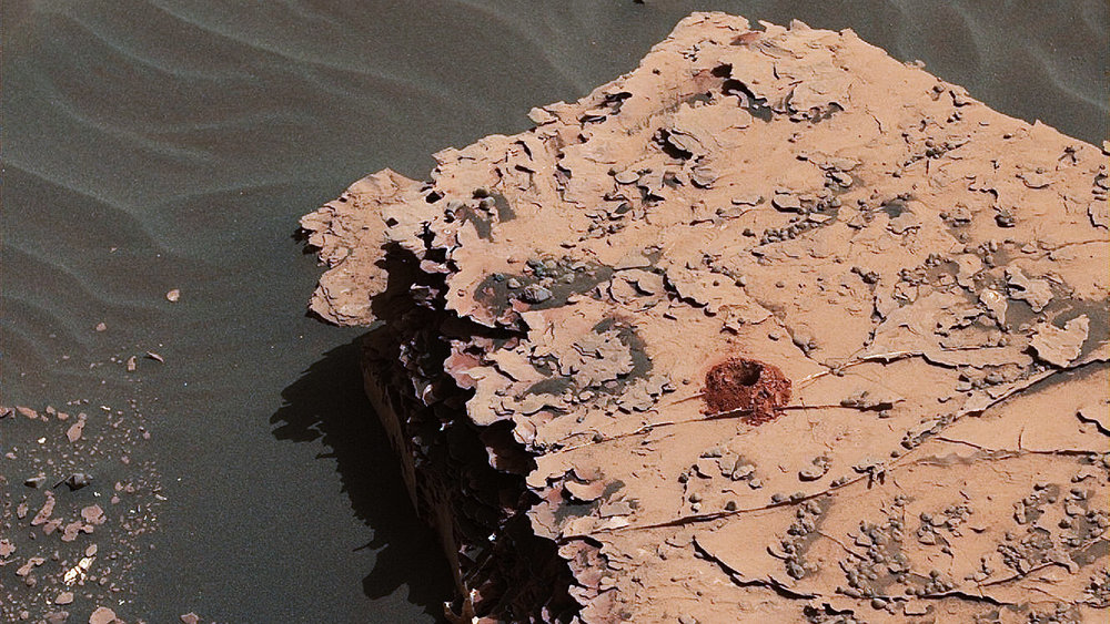 "NASA's Curiosity rover successfully drilled a 2-inch-deep hole in a target called ""Duluth"" on May 20. It was the first rock sample captured by the drill since October 2016. This image was taken by Curiosity's Mast Camera (Mastcam) on Sol 2057. It has been white balanced and contrast-enhanced. - Image Credit: NASA/JPL-Caltech/MSSS"