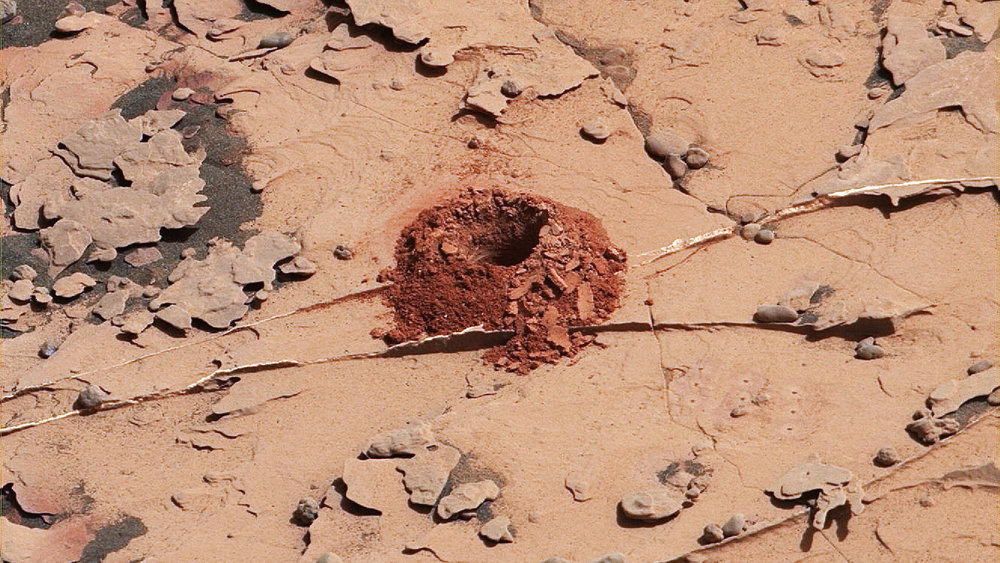 A close-up image of a 2-inch-deep hole produced using a new drilling technique for NASA's Curiosity rover. The hole is about 0.6 inches across (1.6 centimeters). This image was taken by Curiosity's Mast Camera (Mastcam) on Sol 2057. It has been white balanced and contrast-enhanced. - Image Credits: NASA/JPL-Caltech/MSSS