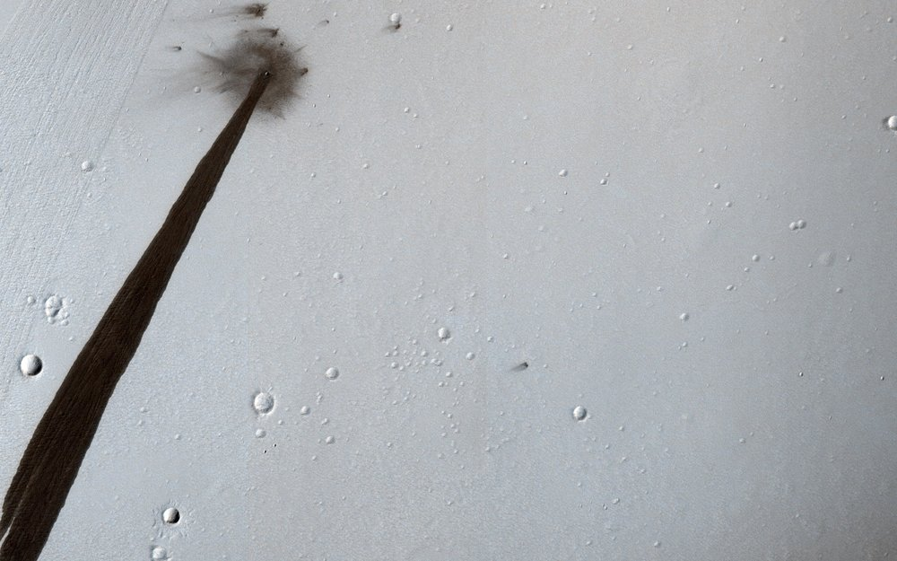 HiRISE image from NASA's Mars Reconnaissance Orbiter (MRO) showing an impact crater that triggered a slope streak. - Image Credit: NASA/JPL/University of Arizona