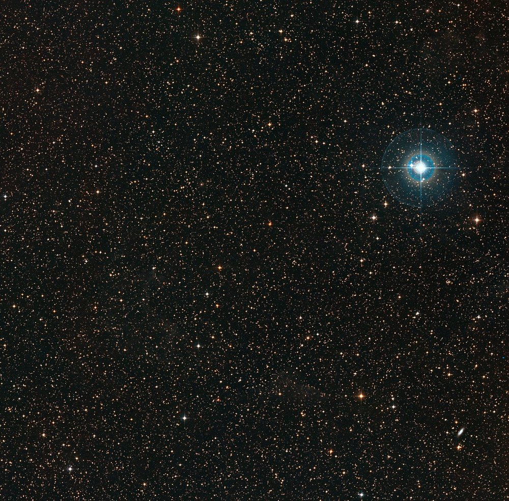 This colourful image shows the sky around the faint orange dwarf star PDS 70 (in the middle of the image). The bright blue star to the right is χ Centauri. - Image Credit:ESO/Digitized Sky Survey 2. Acknowledgement: Davide De Martin