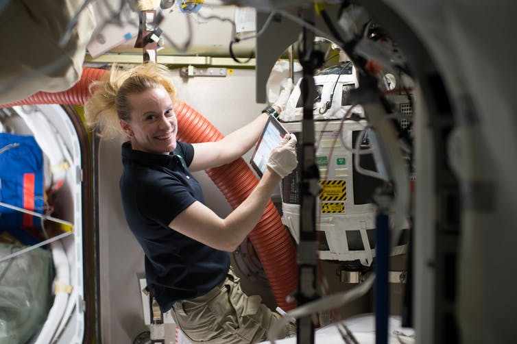 NASA astronaut Kate Rubins works with a Nitrogen/Oxygen Recharge System tank aboard the International Space Station. The tanks are designed to be plugged into the station's existing air supply network to refill the crew's breathable air supply. - Image Credit: NASA