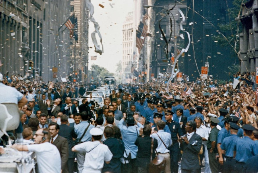 New York City welcomes the Apollo 11 crew in a ticker tape parade down Broadway and Park Avenue. Pictured in the lead car, from the right, are astronauts Neil A. Armstrong, Michael Collins and Buzz Aldrin. The three astronauts teamed for the first manned lunar landing, on July 20, 1969 - Image Credit:  NASA