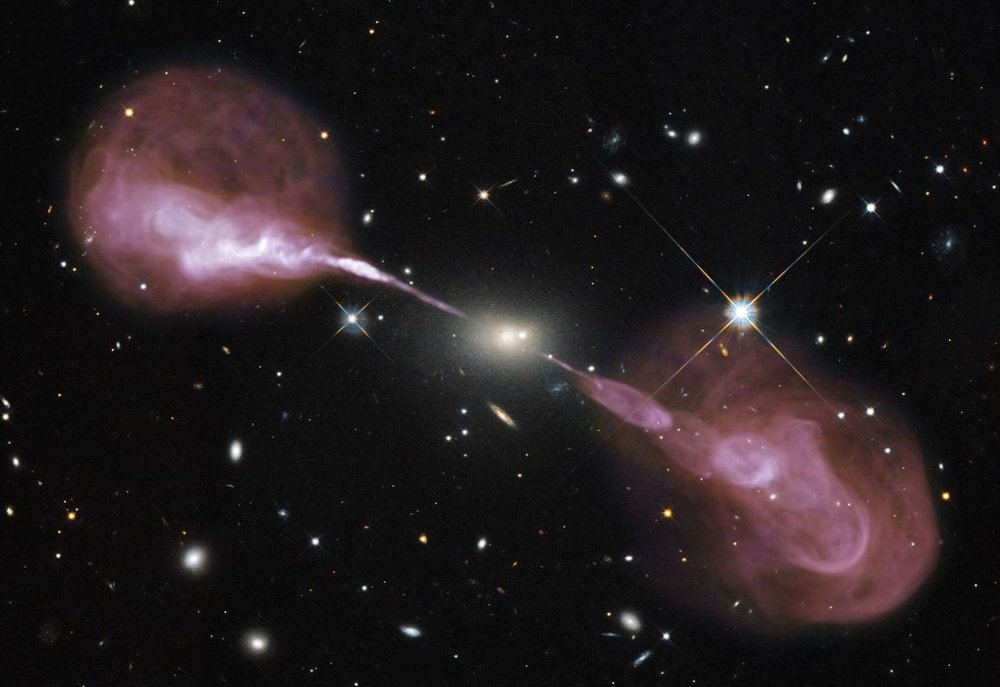 Visible light image of the radio galaxy Hercules A obtained by the Hubble Space Telescope superposed with a radio image taken by the Very Large Array of radio telescopes in New Mexico, USA.- Image Credit:  NASA, ESA, S. Baum and C. O'Dea (RIT), R. Perley and W. Cotton (NRAO/AUI/NSF), and the Hubble Heritage Team (STScI/AURA)