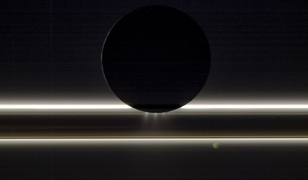 Saturn's moon Enceladus drifts before the rings and the tiny moon Pandora in this view that NASA's Cassini spacecraft captured on Nov. 1, 2009. The entire scene is backlit by the Sun, providing striking illumination for the icy particles that make up both the rings and the jets emanating from the south pole of Enceladus, which is about 314 miles (505 km) across. Pandora, which is about (52 miles, 84 kilometers) wide, was on the opposite side of the rings from Cassini and Enceladus when the image was taken. This view looks toward the night side on Pandora as well, which is lit by dim golden light reflected from Saturn. - Image Credits: NASA/JPL-Caltech/Space Science Institute