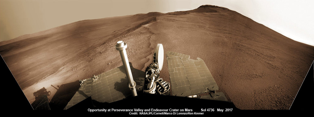 Opportunity rover looks south from the top of Perseverance Valley along the rim of Endeavour Crater on Mars in this partial self portrait including the rover deck and solar panels. Perseverance Valley descends from the right and terminates down near the crater floor. This navcam camera photo mosaic was assembled from raw images taken on Sol 4736 (20 May 2017) and colorized. - Image Credit:  NASA/JPL/Cornell/Marco Di Lorenzo/Ken Kremer/kenkremer.com