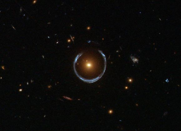 Hubble image of a luminous red galaxy (LRG) gravitationally distorting the light from a much more distant blue galaxy, a technique known as gravitational lensing. - Image Credit: ESA/Hubble & NASA