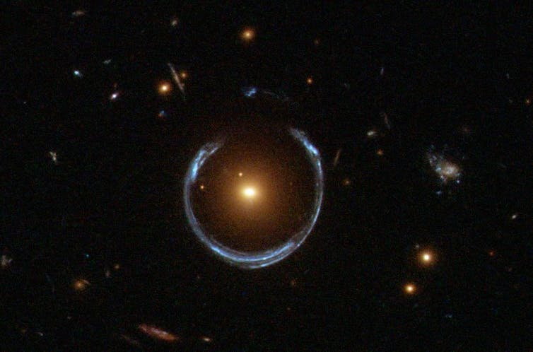 Gravitational lens mirage around a galaxy. - Image Credit: NASA