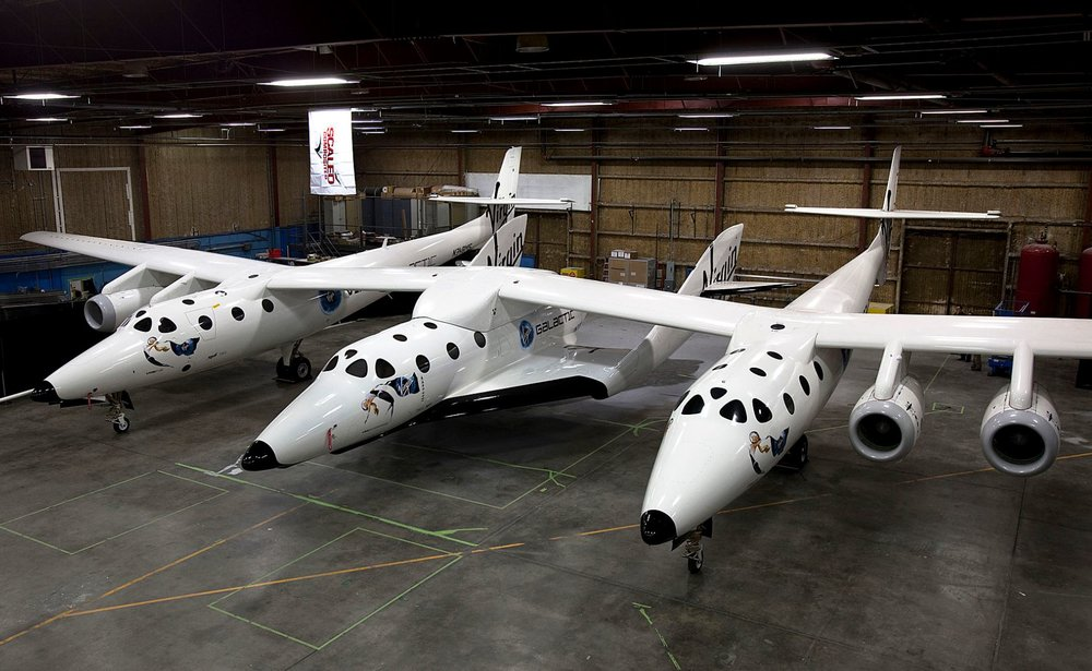 SpaceShipTwo spaceplane (central fuselage) resting under its mothership, White Knight Two - Image Credit:  Virgin Galactic / Mark Greenberg via WikimediaCommons