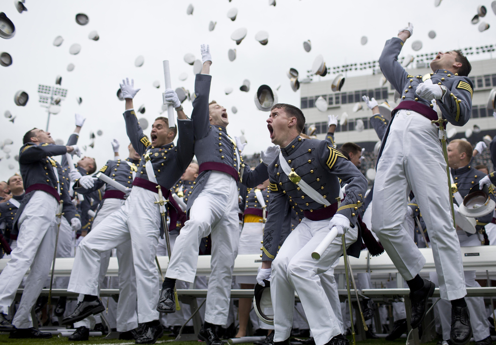 Cadets throw their hats in the air at the end of the graduation ceremony at the U.S. Military Academy on Saturday, May 25, 2013 in West Point, N.Y. Cadets traditionally place pictures, notes, money, and other items inside their hat and leave them on the field for children who rush onto the field following graduation.