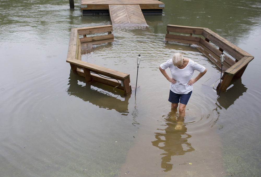Wilma Morgan walks through flood waters on her neighbor's patio Thursday, July 11, 2013 on Riverside Dr. next to the Catawba river in Charlotte, N.C. Heavy rain across the region caused flash floods across the area. nycpr
