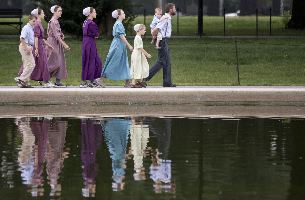 A family walks along the Lincoln Memorial Reflecting Pool on July 8, 2013 in Washington, D.C. nycpr