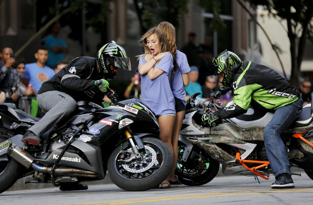 Jason Britton, left, and Eric Hoenshell, right, circle around Samantha Taylor, center facing forward, and Nicole Yowell, center facing away, during a stunt show at Ray Price Capital City Bikefest on Friday, September 26, 2014 on Hargett Street in Raleigh, N.C. Taylor and Yowell work for Team Powersports and were unexpectedly invited to participate in the show.