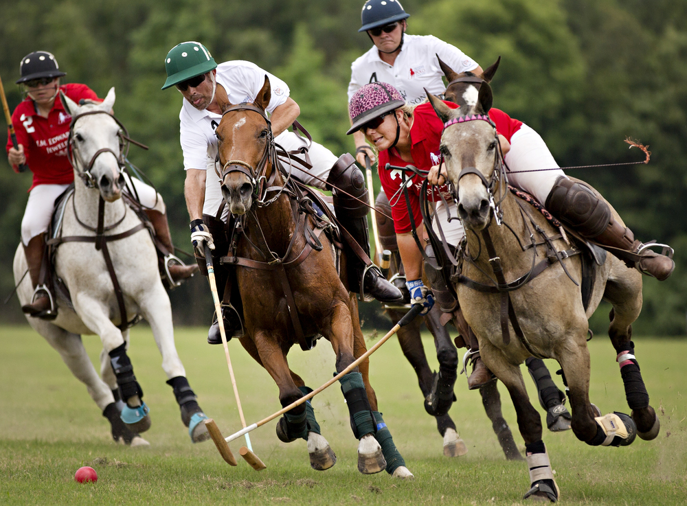 Jessica Riemann, left, Alan Hale, second from left, and David Brooks, second from right, ride behind Jolie Liston as she swings to hit the ball during a match at the John H. Triangle Charity Polo Classic Benefit at MacNair's Country Acres on Sunday, June 8, 2014 in Raleigh, N.C.