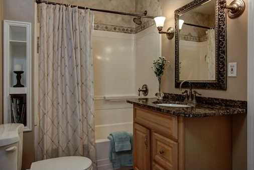 The bathroom of a home staged by   D Organizing  .