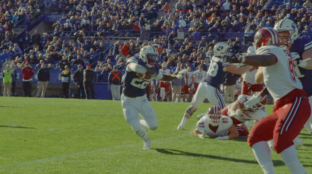 BYU running back Squally Canada evades UMASS defenders.