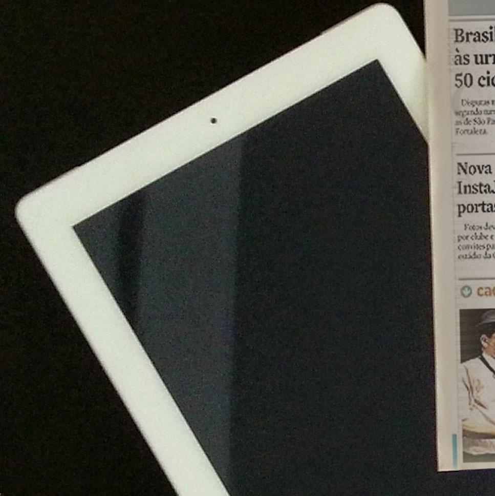 (Descrição da imagem: Um ipad em cima de uma mesa preta)
