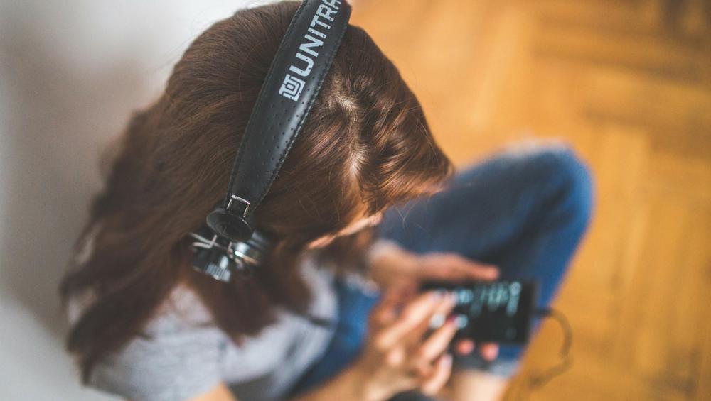 (Descrição da imagem: Mulher seleciona um conteúdo no celular. Ela está usando fones de ouvido ligados ao celular. A mulher está sentada no chão de madeira da sua casa)