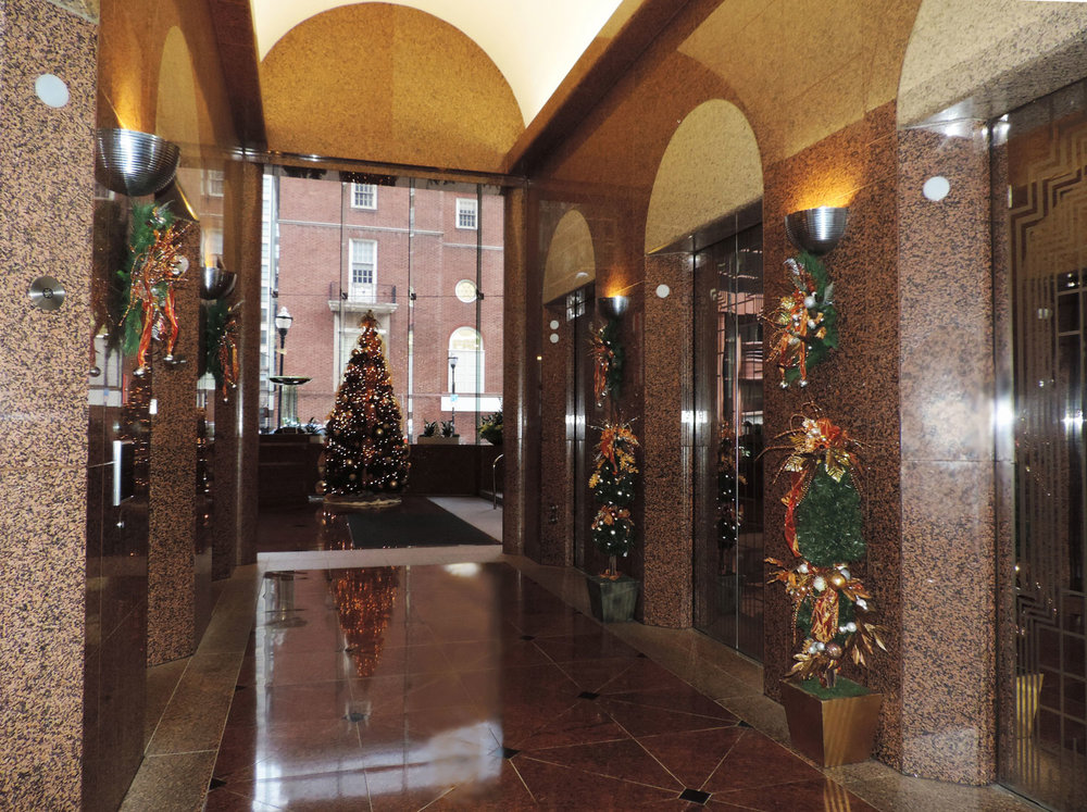 elevator lobby decorated with holiday greenery and christmas trees