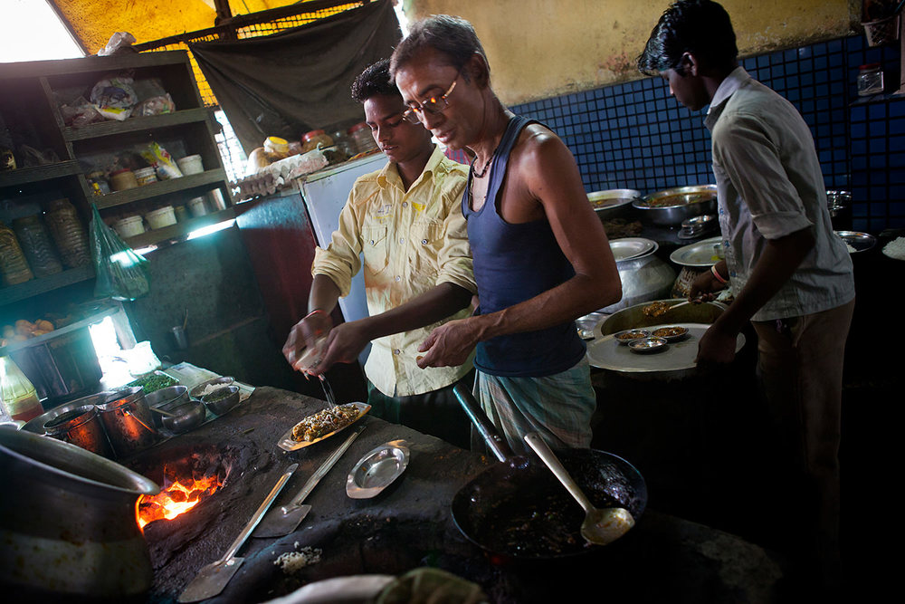 Three men working in a kitchen in a small restaurant in Bokaro- India