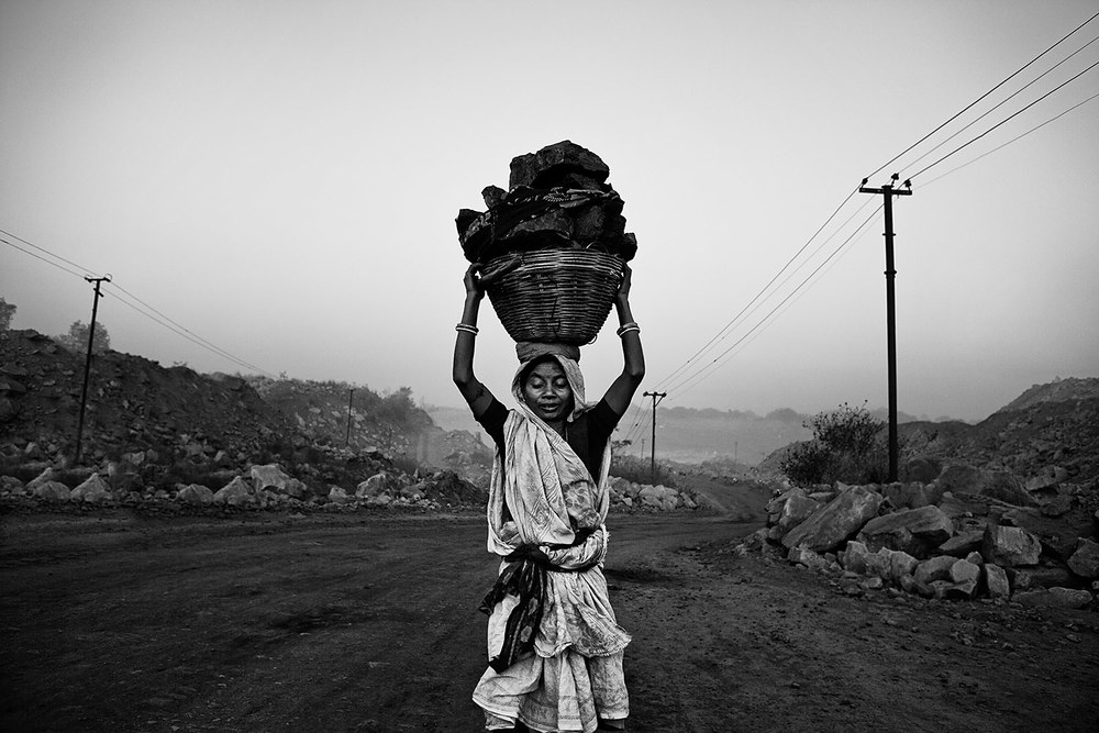 A woman carrying a basket full of coal in a mine.  Jahria-India