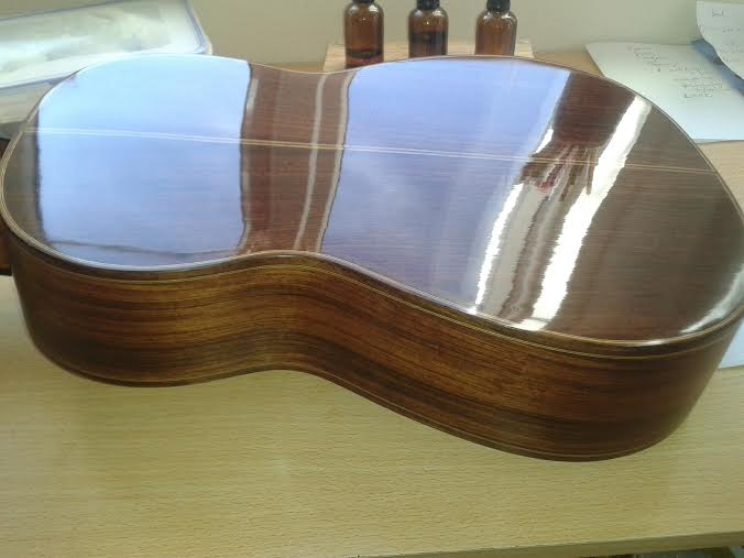 The rosewood guitar above has been French Polished with shellac in the traditional way, producing a high gloss mirror finish.