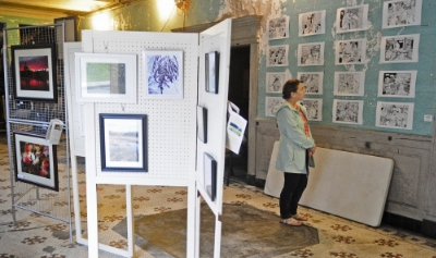 Maureen Booth looks at art on display Friday in the Colonial Theatre lobby during the Raw Spaces: Art Walk in downtown Augusta.Staff photo by Joe Phelan