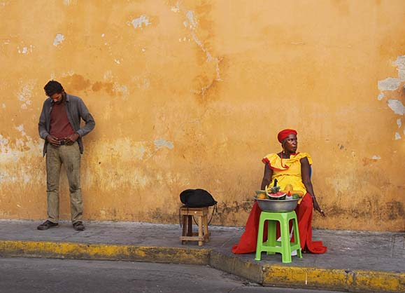 The Two Faces of Cartagena. On the right, the tourist face, a Palenquera in traditional dress. On the left a homeless man, representing another side of the city, not often seen by the tourists.