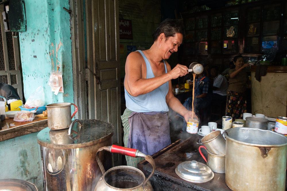 U Toe Kyinn a preparar chá com leite