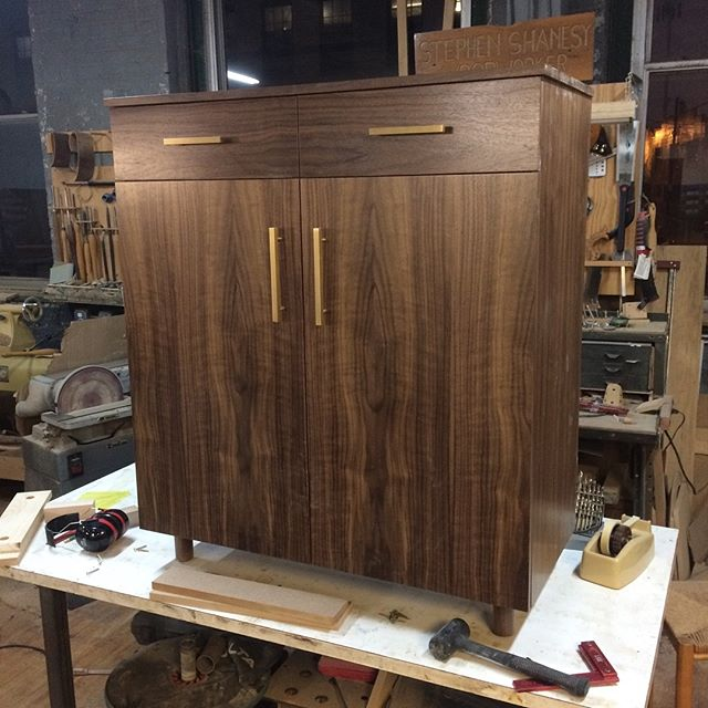 Finishing up for the day with final assembly of this lovely walnut custom cabinet. Client picked these brass pulls which really set it off. Nice way to start the week. #cincymade #cabinetmaker #woodworking #interior