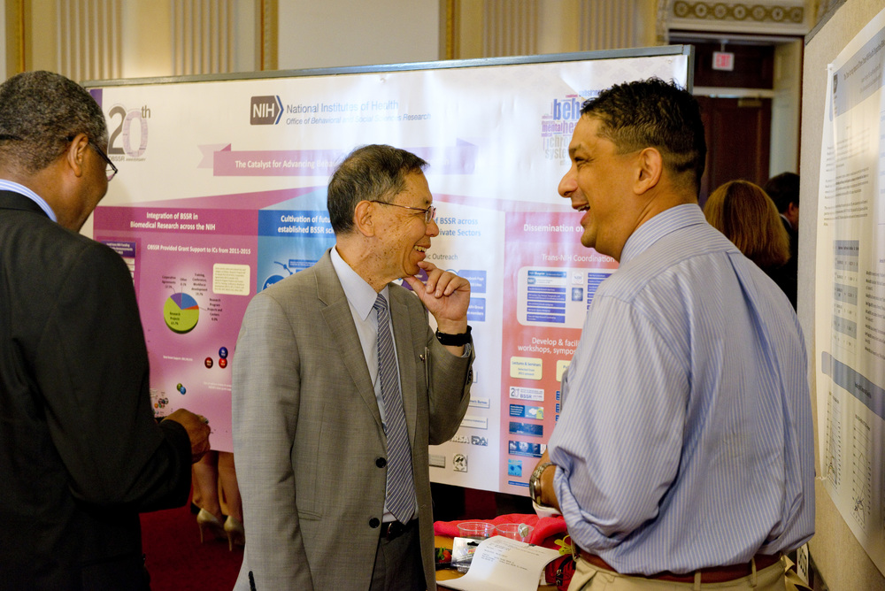 NIH Center for Scientific Review Director Richard Nakamura (center) with Mike Spittel  (right) of OBSSR at the OBSSR 20th anniversary poster session on Capitol Hill. (Credit: Charles Votaw).