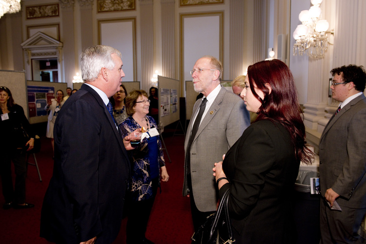 Bill Riley (left), Acting Director of the NIH Office of Behavioral and Social Sciences Research (OBSSR) greets U.S. Rep. Dave Loebsack (D-IA) at the OBSSR 20th anniversary poster session on Capitol Hill. (Credit: Charles Votaw)