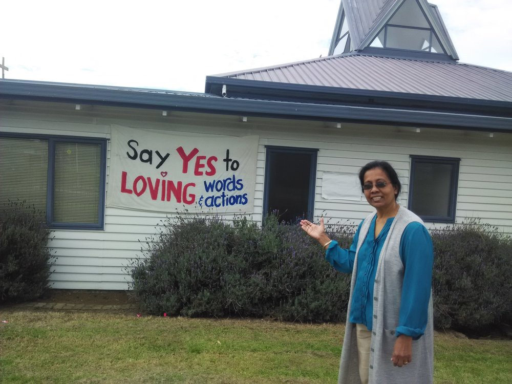 "Dr. Suseela Mathew pointing out a banner placed up on the side of a building to gently remind all reading it to be aware of ""Basics"""