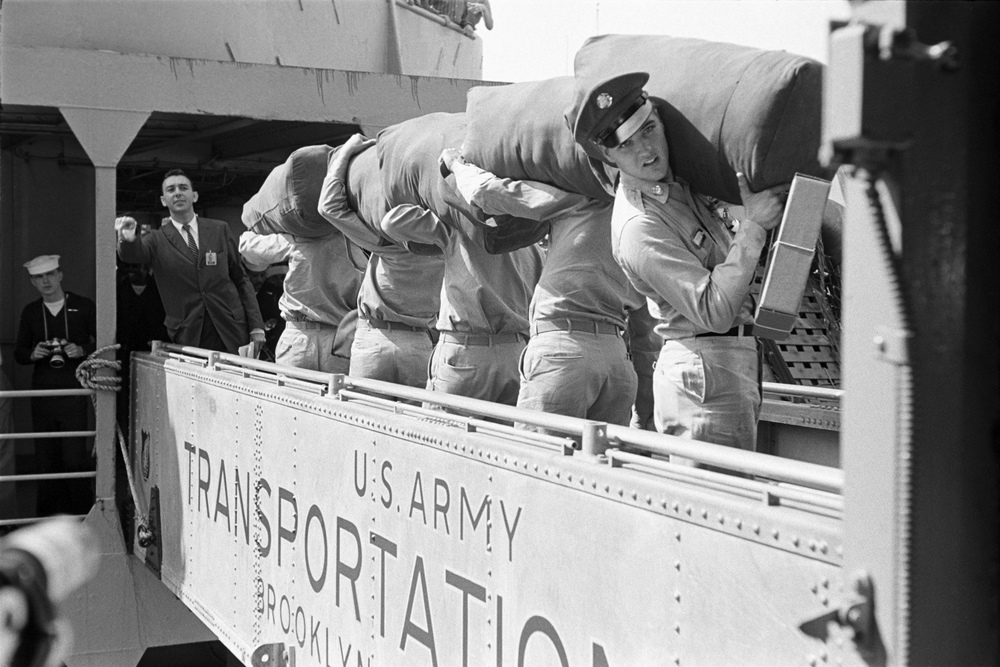 Elvis and fellow soldiers of Company D 1st Battalion 32nd Armor, 3rd Armored Division walk the gangplank of the <i>USS Randall</i>.  The maneuver was repeated several times for the photographers.