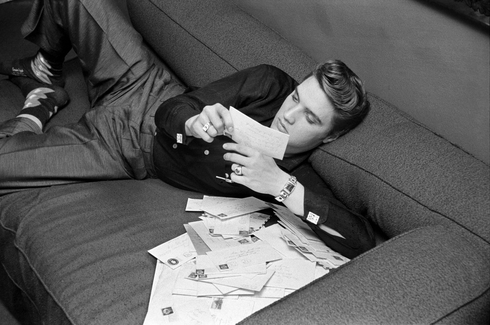 Elvis reading his fan mail inside his suite at the Warwick Hotel in New York City.