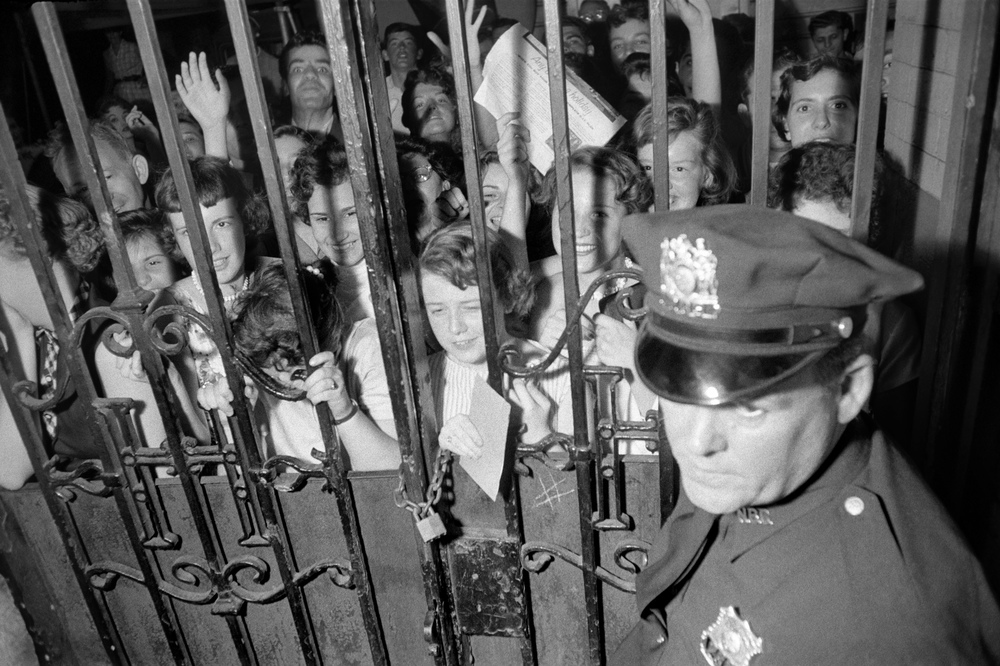 Elvis's fans find themselves behind bars, while waiting outside the NBC Studio in New York City. 1956
