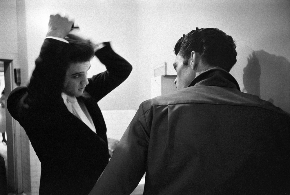 Junior Smith gives encouragement while Elvis combs his hair in the men's room of the studio.