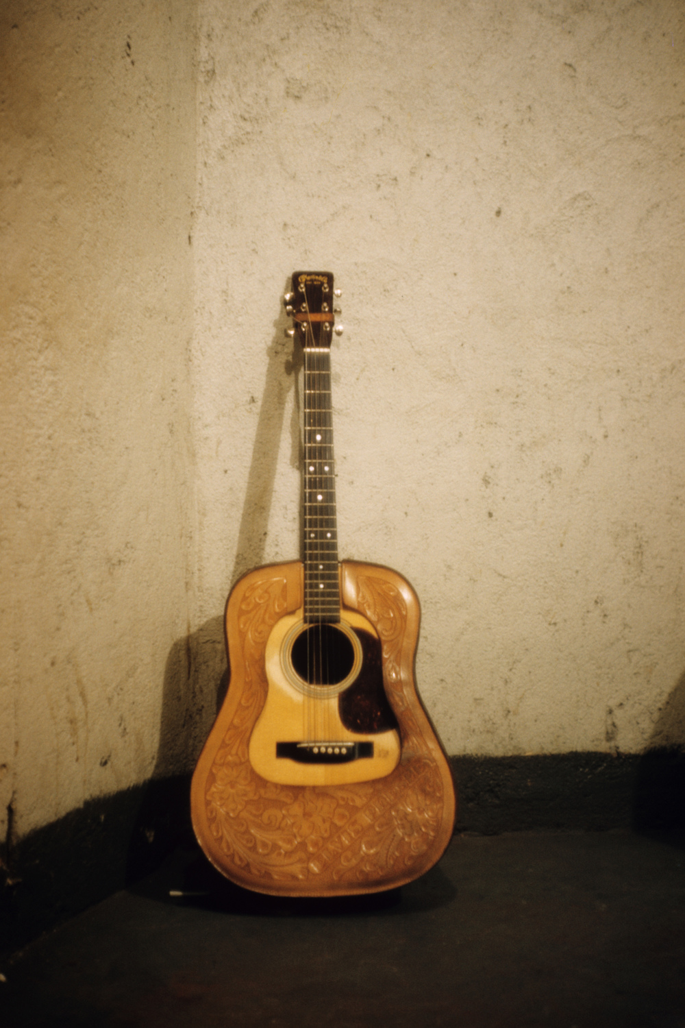"Elvis's Martin guitar, with a tooled leather cover, stands upright against the wall during the recording session of ""Hound Dog."""
