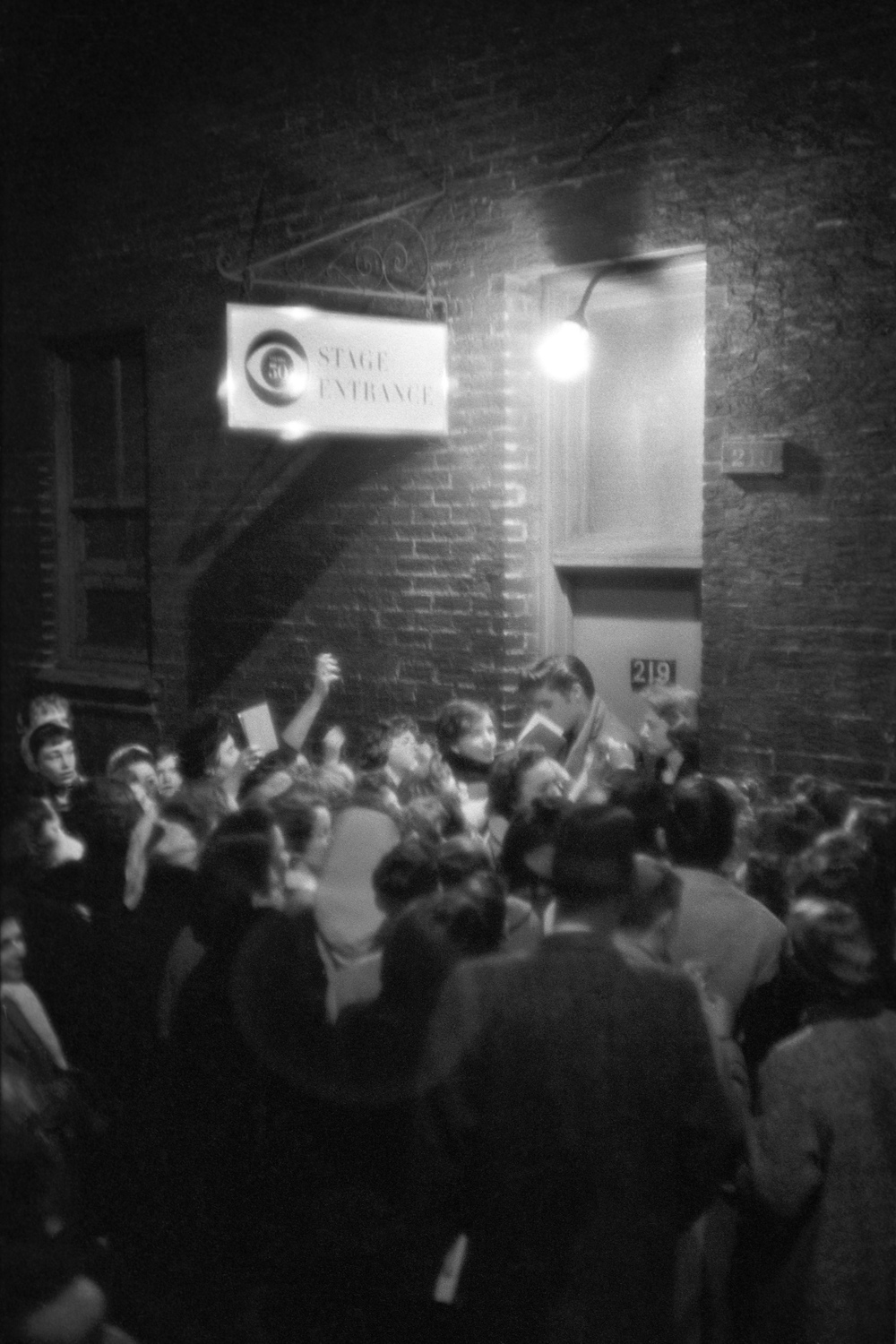 Late at night Elvis's fans gather outside the stage door to CBS studios.