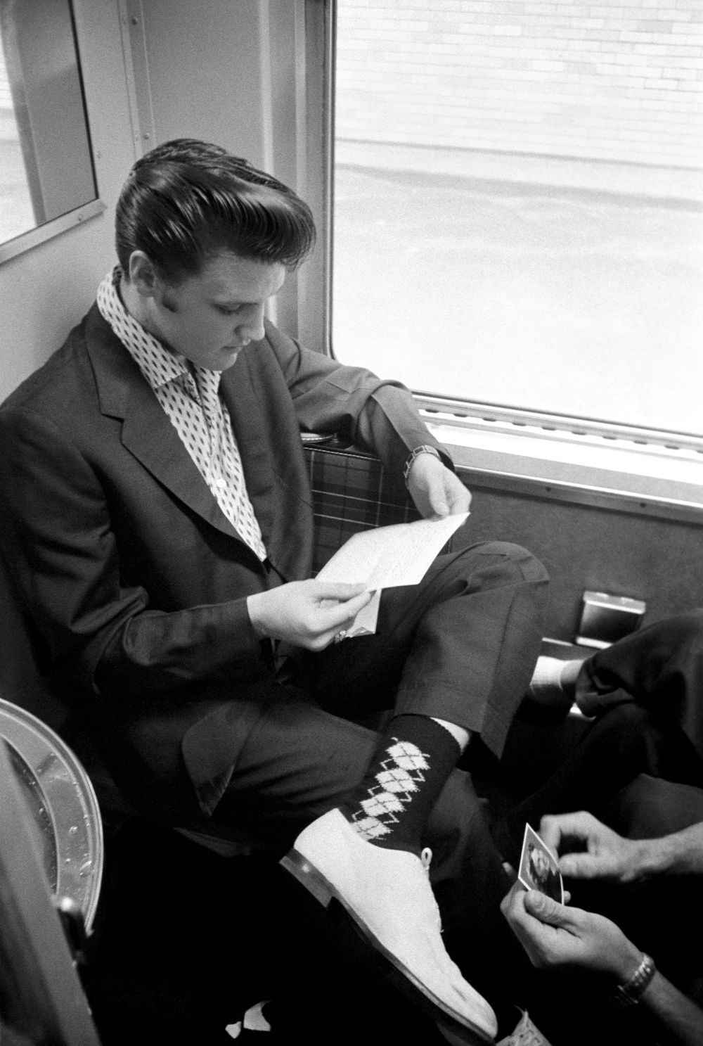 Aboard the train to memphis, Elvis reads some of his fan mail.