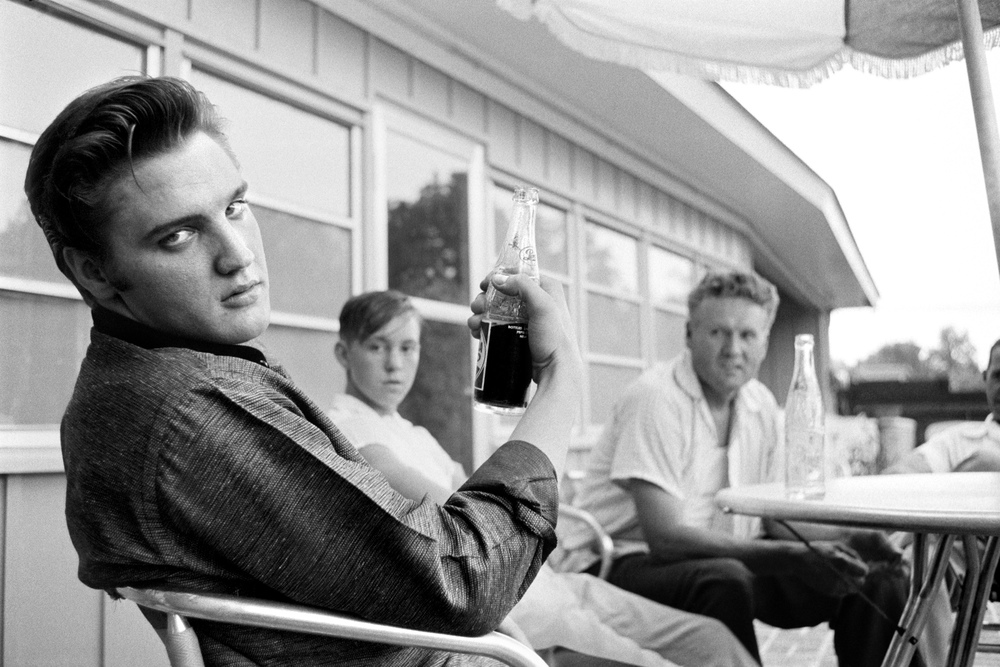 Elvis gives Al Wertheimer his patented stare, wth his cousin Bobby and his father in the background.