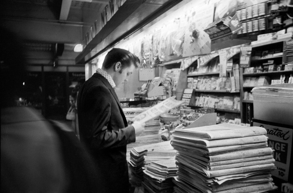 At Penn Station, Elvis stops at a newsstand to read a front-page story about a midair collision of planes over the Grand Canyon.