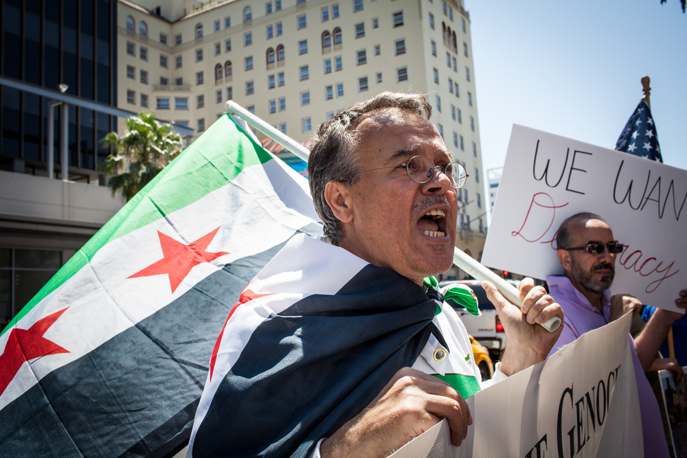 "Protester Mazen Almoukdad shouts, ""We want democracy!"" in front of the TLC Chinese Theater."