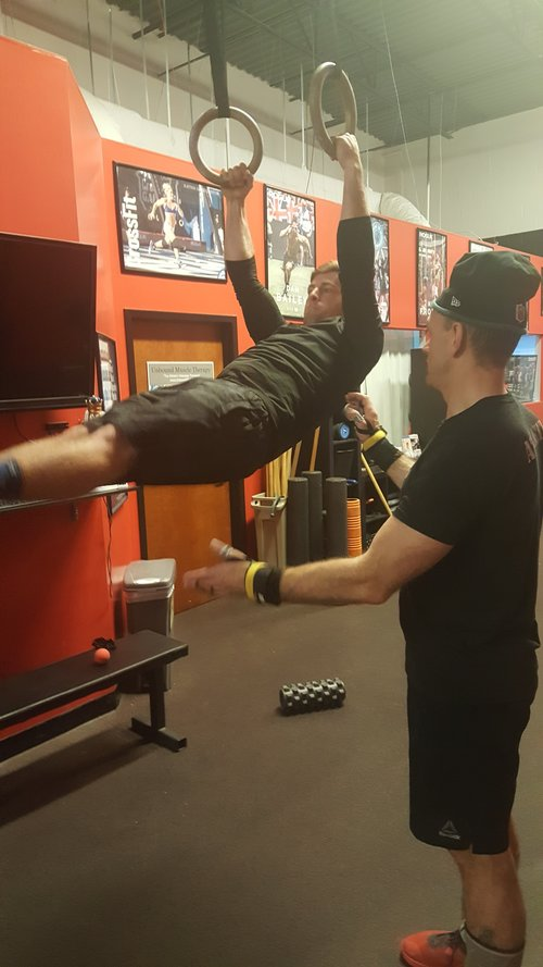 CFCM Head Coach Mike works with Justin on maintaining good hollow position through a kipping swing on the rings.