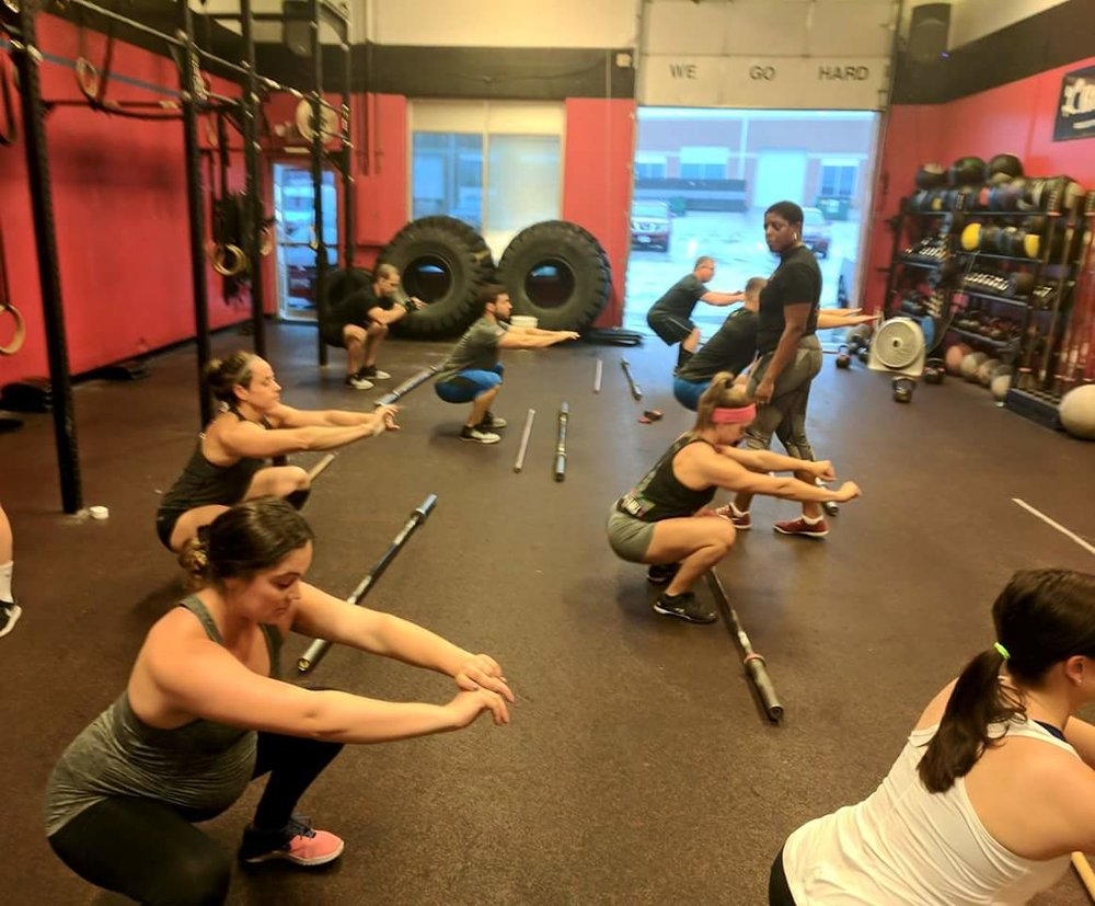 CrossFit Level 2 Coach Kim reviews the air squats with a class prior to the day's workout.   CFCM's CrossFit Trainers use these opportunities to correct and improve basic positions prior to the days workout.