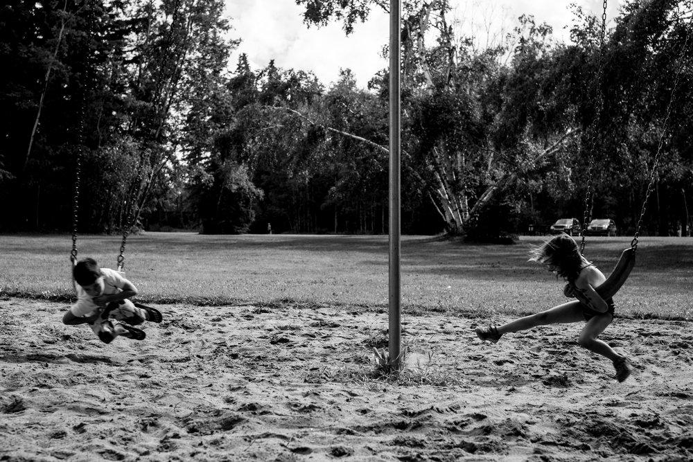 Kids crazy swinging at the lake playground
