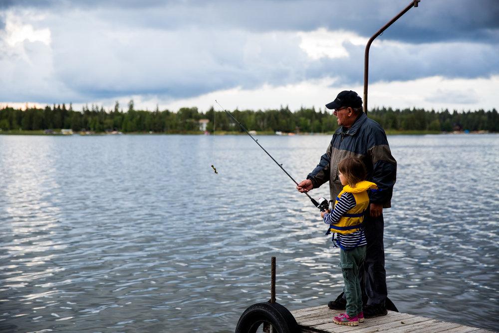 grandpa and grandchild fishing at lake